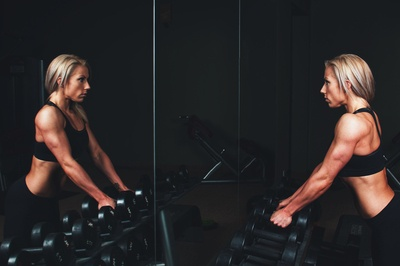 Woman Wearing Black Top Top Holding Black Dumbbells Standing in Front