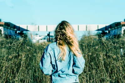 Woman Wearing Blue Denim Jacket Standing on Grass Field