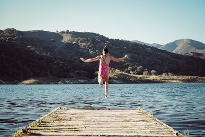 Woman Wearing Pink Top Jumping Towards Water