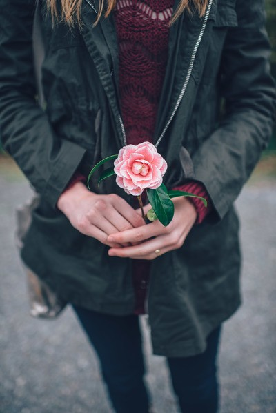 Woman in Black Leather Jacket Holding Pink Flower