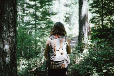 Woman in Sleeveless Top And Backpack Surrounded By Trees