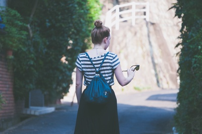 Woman in Striped Shirt with Backpack Holding Sunglasses While Walking on
