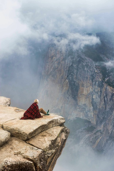 Woman in front of a cloudy mountain