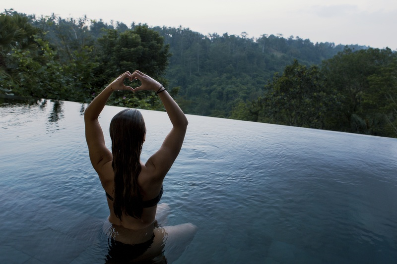 Woman in infinity Pool Making Heart Hand Gesture Facing Green Leafed