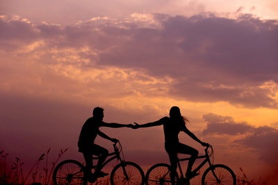 Woman on Bike Reaching For Man's Hand Behind Her Also on