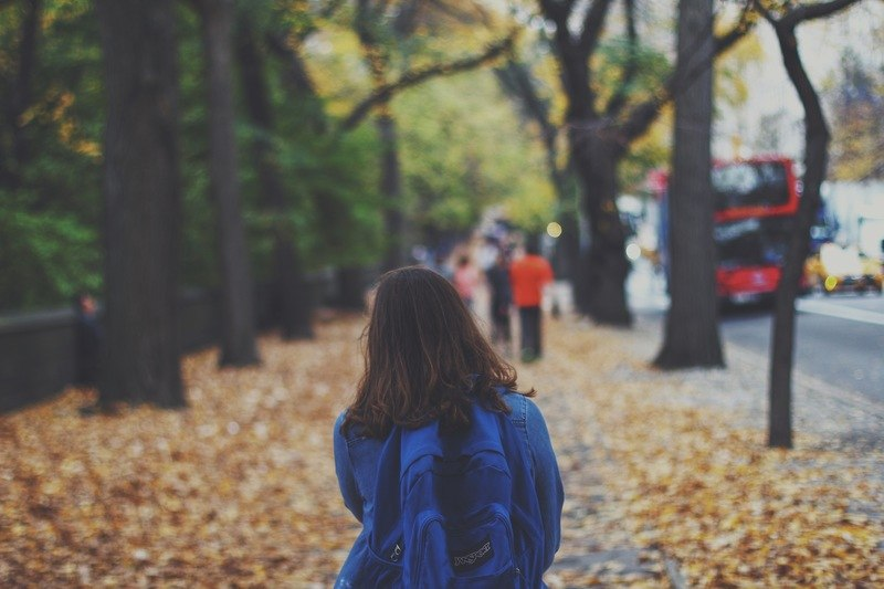Woman with Blue Backpack on Street Full of Fallen Leaves