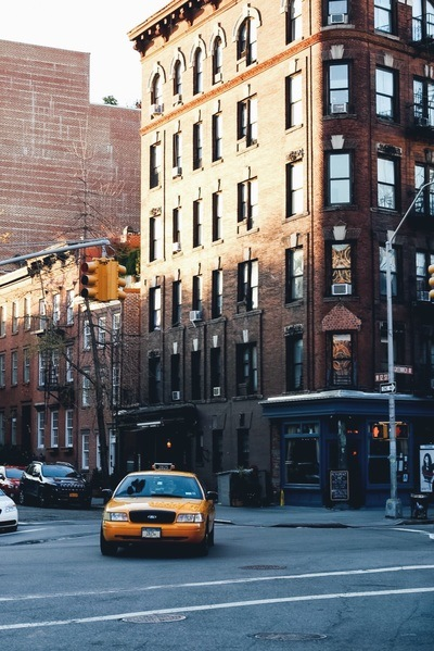 Yellow Taxi in Front of Brown Brick Building