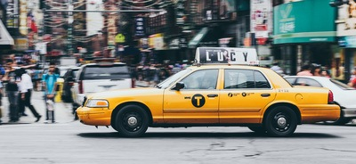 Yellow Taxi on Concrete Road