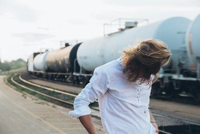 Young Man By Trains At Sunset