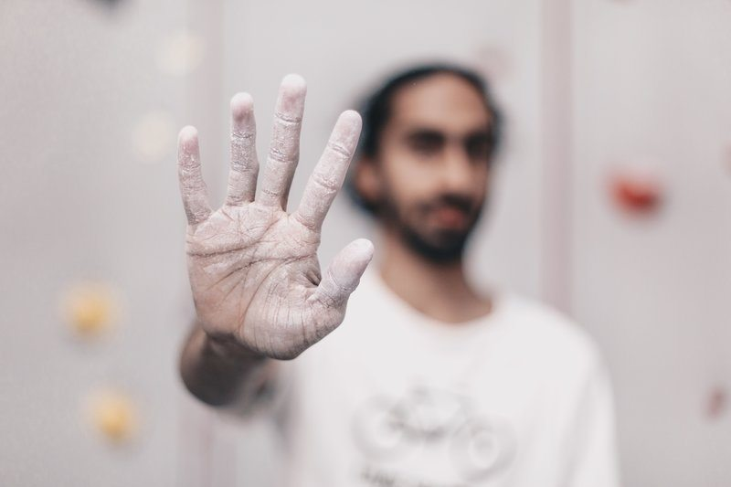 Young Man Holding Out Chalk Covered Hand