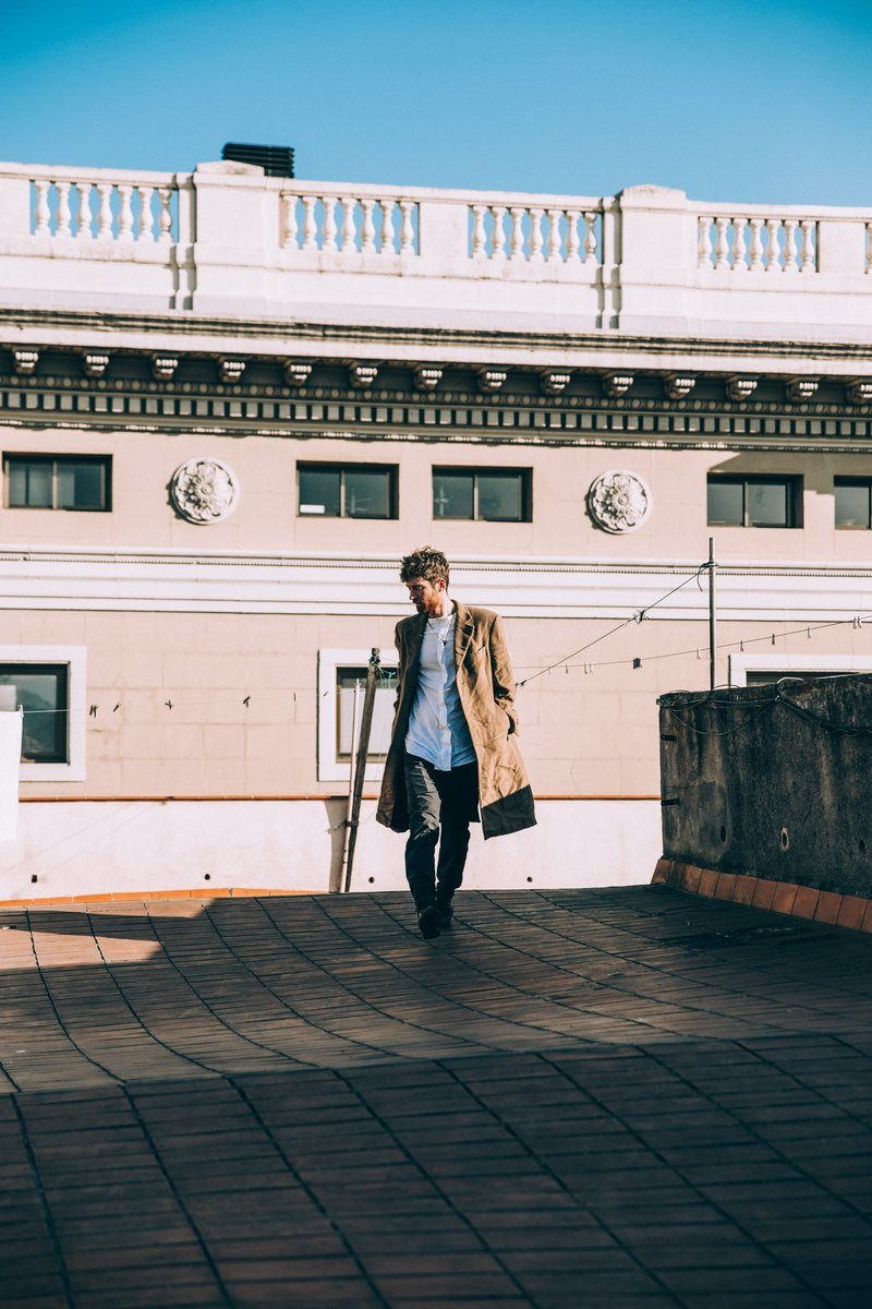 Young Man On Rooftop In Brown Coat