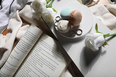 Reading a book with macarons