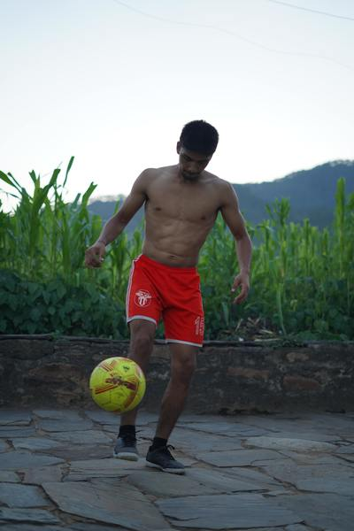 Young man playing with green soccer ball