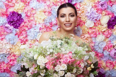 Woman posing in front of colorful flower background